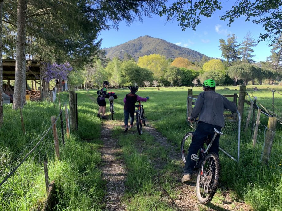 Image Of Cyclists On Baton River Property With Mountain In The Background